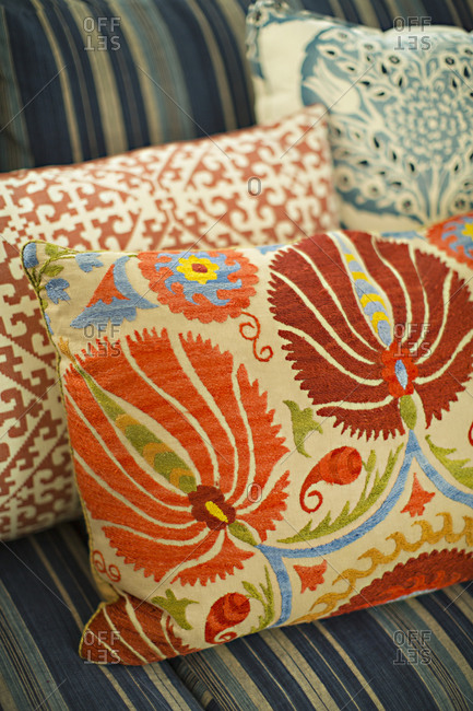Three different embroidered cushion on a couch