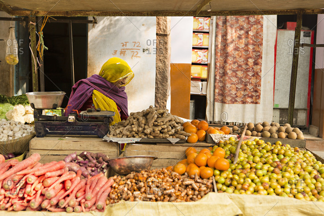 India - January 14, 2014: Woman selling vegetables and fruits at a market along the road from Jaipur to Jodhpur