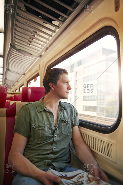 Young man staring out of a train window
