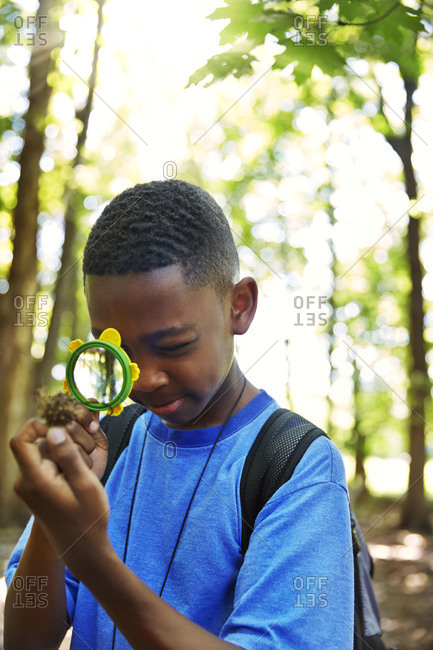 Young boy looking trough a magnifier in a forest