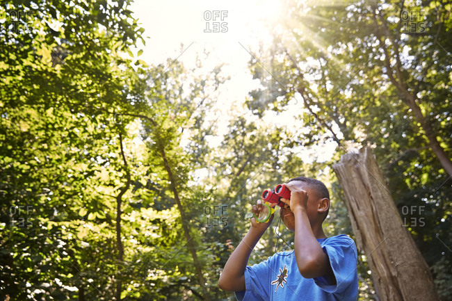 Young boy looking trough a binocular in a forest