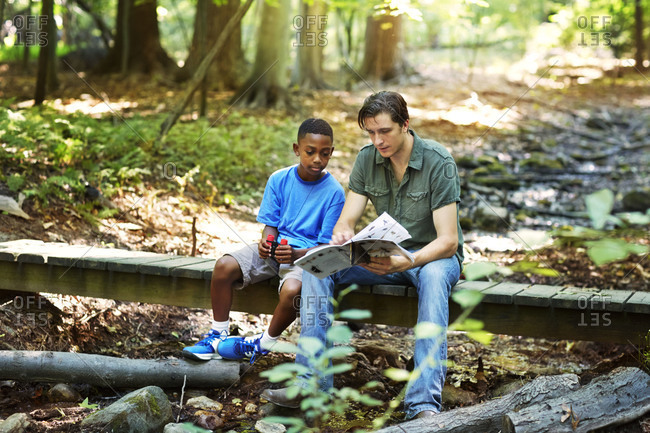 Man showing a book to a boy in a forest