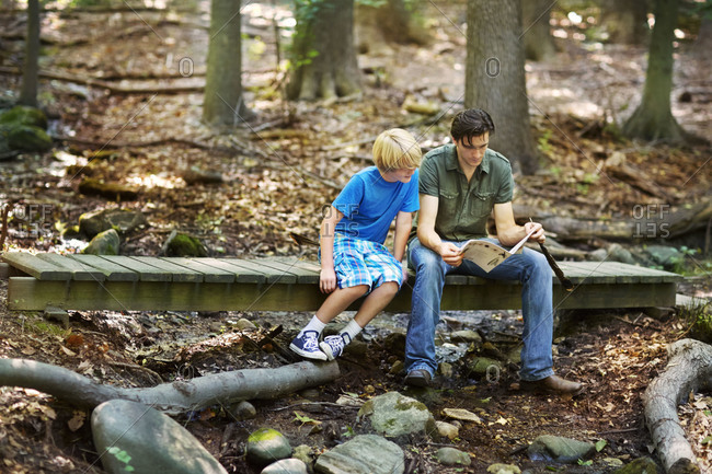 Man with a young boy looking at a book in a forest