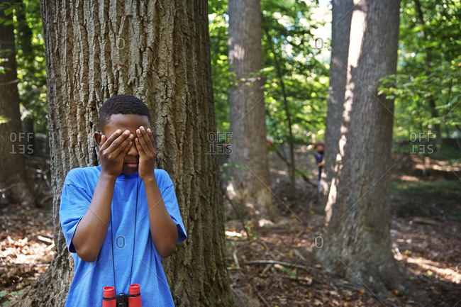 Children playing hide and seek in a forest