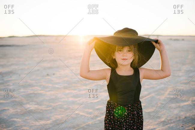 Little girl adjusting broad hat in the desert