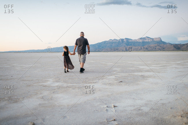 Father and daughter walking in a desert valley