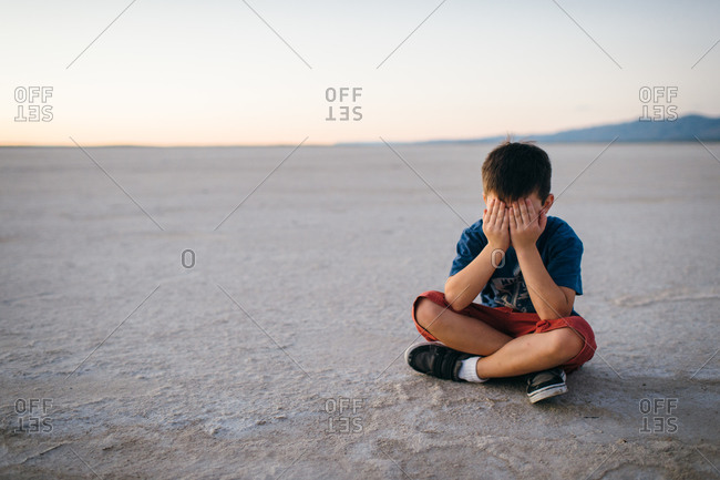 Boy sitting covering eyes in desert valley