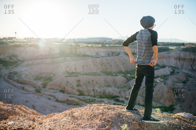 Teenager overlooking canyon in the desert