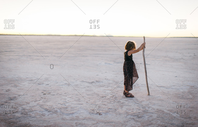Girl with stick in the desert