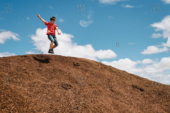 Boy jumping off a large pile of mulch