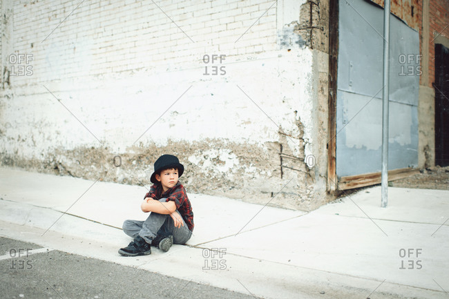 Young boy sitting alone on the curb