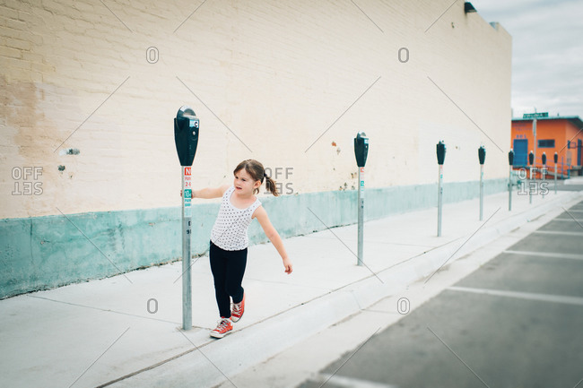 Young girl playing with parking meters