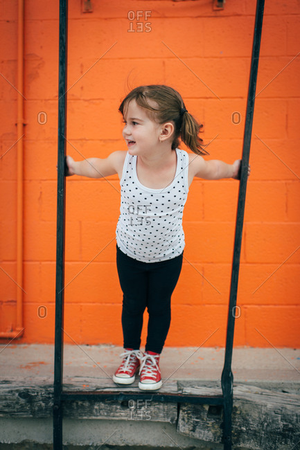 Little girl playing by an orange wall