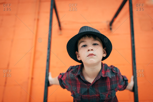 Young boy in hat playing by orange wall