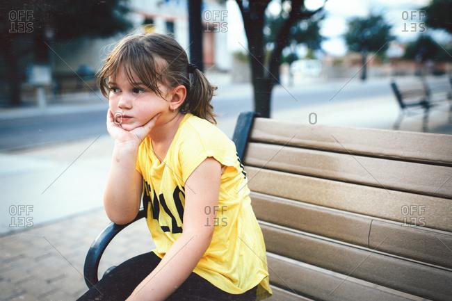 Bored little girl waiting on bench