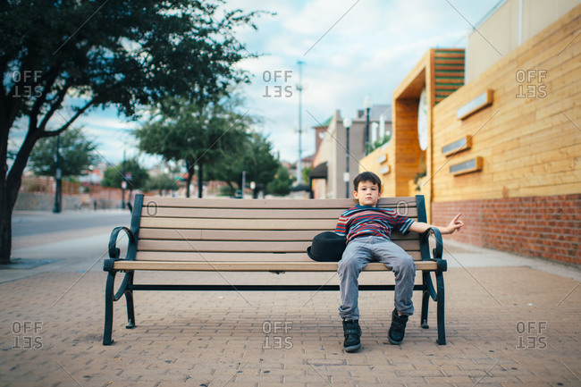 Little boy with hat on park bench