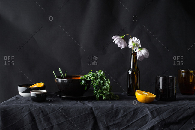 Still life of dark props with flowers and herbs