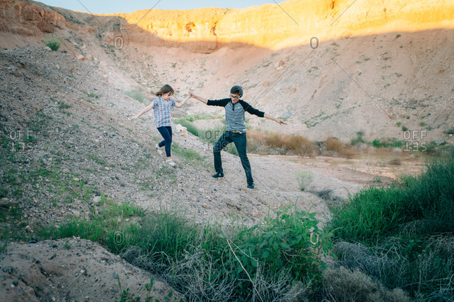 Teenaged boy and little girl playing in desert canyon