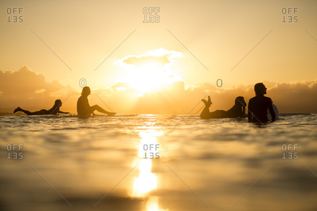 Surfers wait for waves in the sunset
