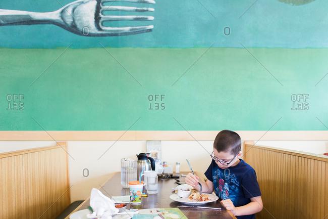 Boy eating in a diner