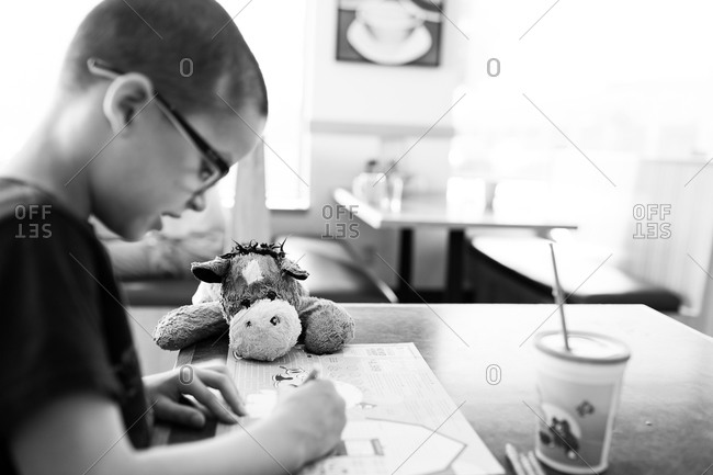 Boy sitting in a diner with a plush horse
