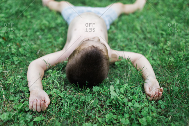 Boy sprawled out on the grass