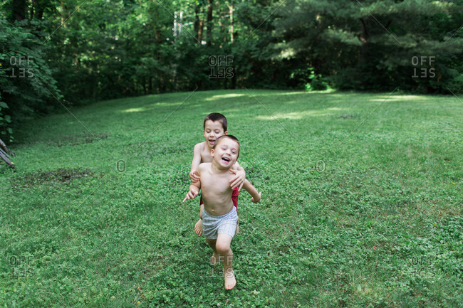 Boy chasing his brother in the garden
