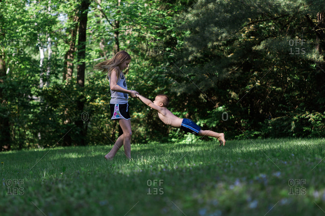 Girl spinning her brother around