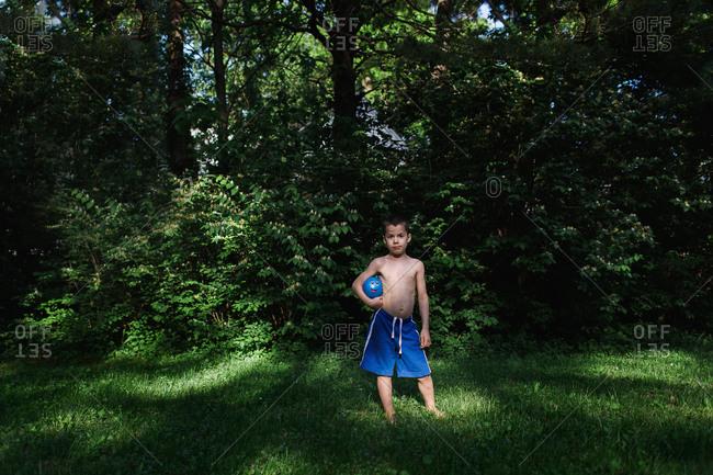 Boy holding a ball under his arm in the garden