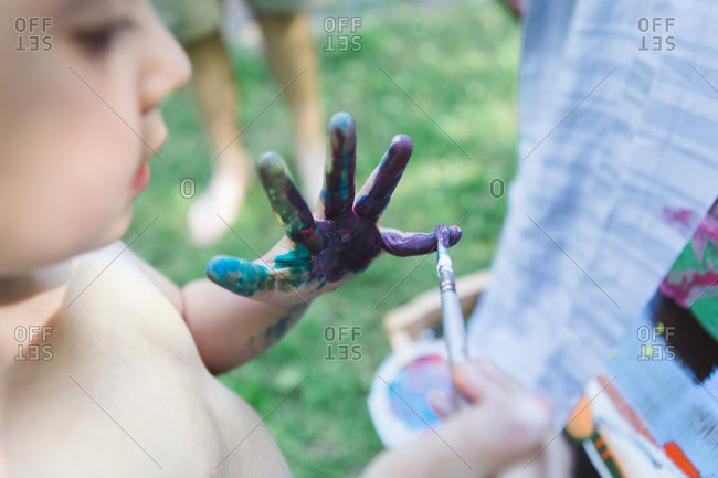 Close up of boy smearing paint over his hand