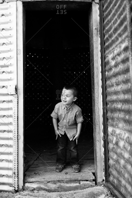 Boy standing in the doorway of a warehouse