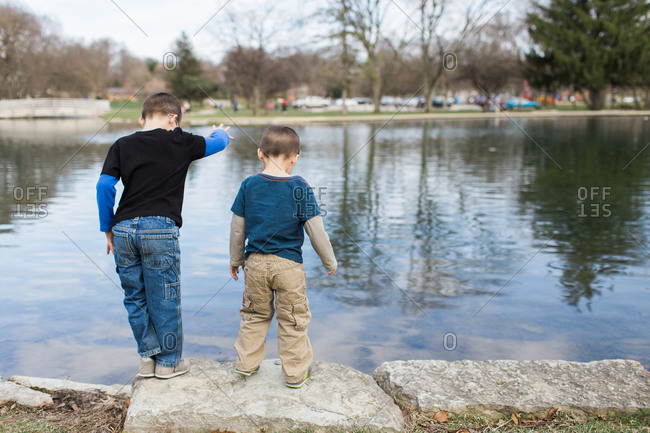 Two boys looking at a pond