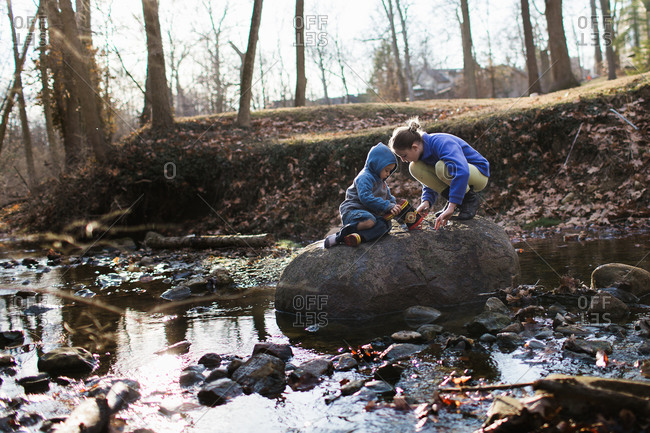 Children playing on a rock at a river