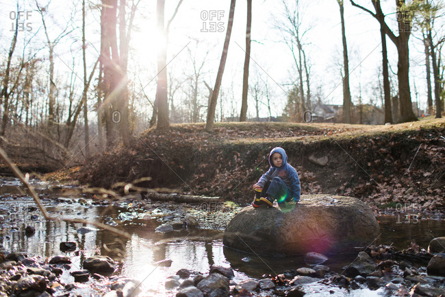 Young boy sitting on a rock at a river