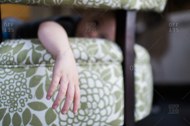 Young boy lying on a chair