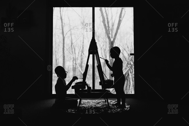 Silhouettes of young boys painting in a room