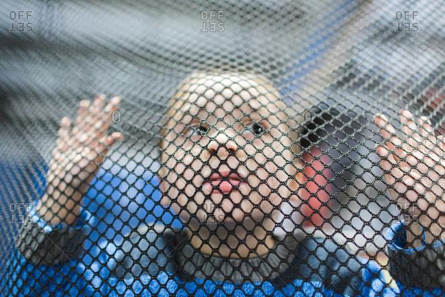 Young boy looking through a net