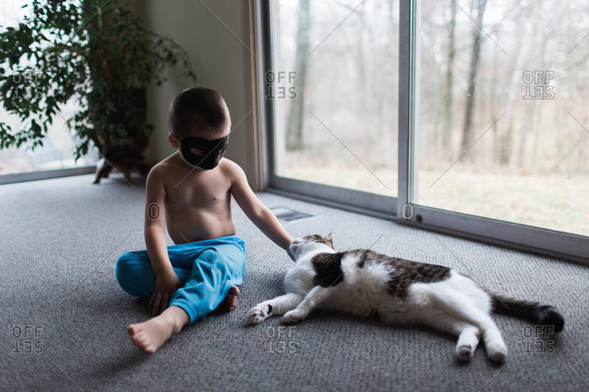 Young boy in a mask petting a cat