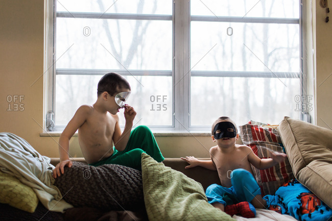 Young boys in masks sitting on a couch