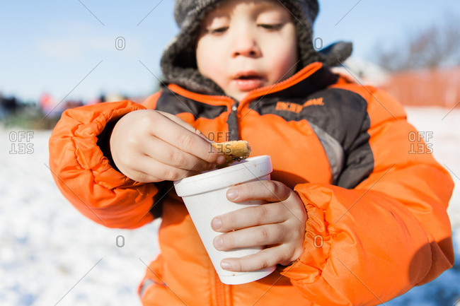 Young boy dunking biscuit in a hot beverage