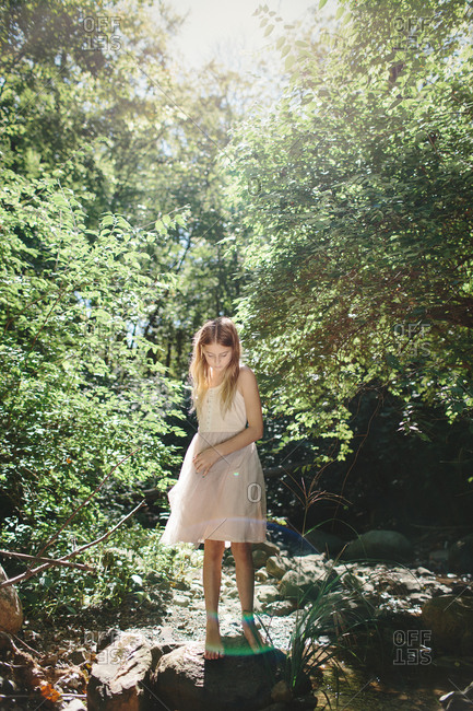 Young girl standing on a rock in a forest