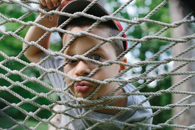 Young boy peeking through a net