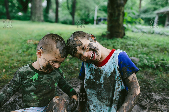 Playful boys sitting in mud
