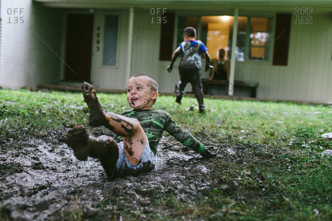 Young boys playing in the mud