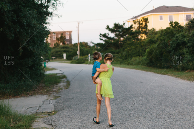 Young girl carrying her brother on a street