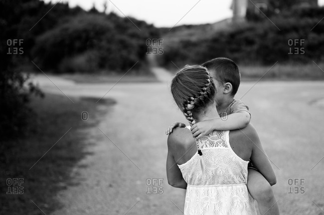 Young girl carrying her brother