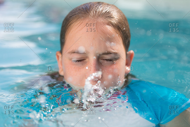 Young girl spitting water in a pool