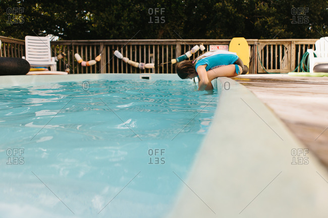 Young girl sitting on a poolside