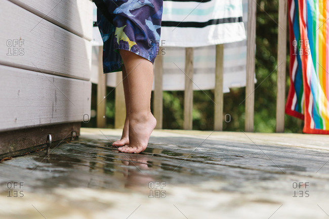 Young boy tiptoeing at a poolside
