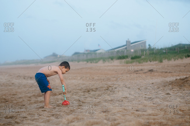 Young boy digging with a toy shovel on a sandy beach